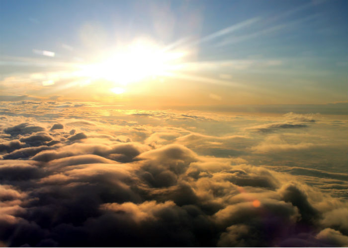 Sun rising above clouds